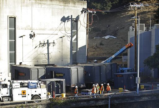 Crews work to connect generators in effort to keep the Caldecott Tunnel open to traffic during a possible power outage at noon on Wednesday, Oct. 9, 2019, in Oakland, Calif. Pacific Gas & Electric has cut power to more than half a million customers in Northern California hoping to prevent wildfires during dry, windy weather throughout the region.