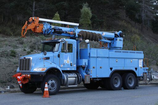 PG & E maintenance truck waits near the Caldecott Tunnel on Wednesday, Oct. 9, 2019, in Oakland, Calif. Pacific Gas & Electric has cut power to more than half a million customers in Northern California hoping to prevent wildfires during dry, windy weather throughout the region.