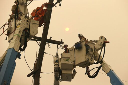 FILE - In this Nov. 9, 2018, file photo, Pacific Gas & Electric crews work to restore power lines in Paradise, Calif. Two years to the day after some of the deadliest wildfires tore through Northern California wine country, two of the state's largest utilities were poised Tuesday, Oct. 8, 2019, to shut off power to more than 700,000 customers in 37 counties, in what would be the largest preventive shut-off to date as utilities try to head off wildfires caused by faulty power lines.