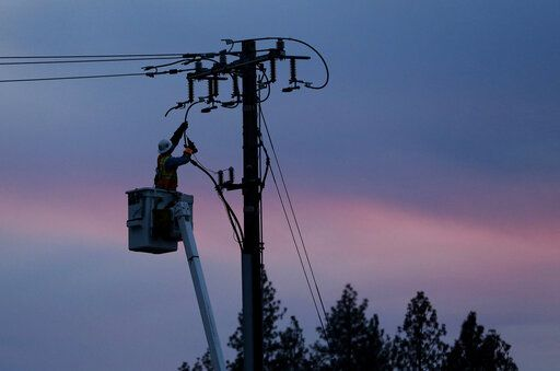 FILE - In this Nov. 26, 2018, file photo, a Pacific Gas & Electric lineman works to repair a power line in fire-ravaged Paradise, Calif. Two years to the day after some of the deadliest wildfires tore through Northern California wine country, two of the state's largest utilities were poised Tuesday, Oct. 8, 2019, to shut off power to more than 700,000 customers in 37 counties, in what would be the largest preventive shut-off to date as utilities try to head off wildfires caused by faulty power lines.