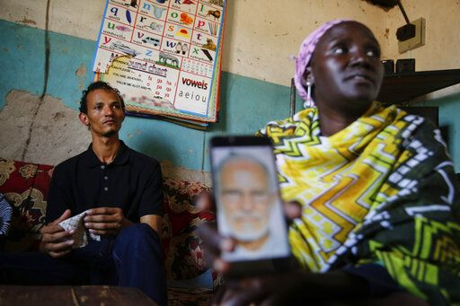 Gerald Erebon sits with his aunt, Scolastica Apayo, as she holds a phone displaying a photo of the Rev. Mario Lacchin, during an interview at her home in the Isiolo area of the Archers Post settlement in Kenya on Sunday, June 30, 2019. Scolastica said her sister, Sabina Losirkale, finally told her the secret in 2012, two weeks before she died. 'œNow that my days are over,'� her sister told her, she could reveal all: 'œWhen Gerald will ask you who's his father, just tell him: Father Mario.'�