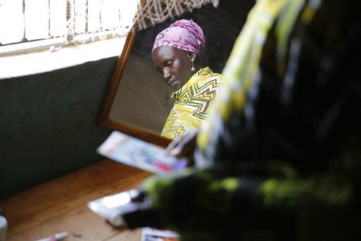Scolastica Apayo, sister of the late Sabina Losirkale, looks through her old photos in the Isiolo area of the Archers Post settlement in Kenya on Sunday, June 30, 2019. Scolastica said her sister finally told her the secret in 2012, two weeks before she died. 'œNow that my days are over,'� her sister told her, she could reveal all: 'œWhen Gerald will ask you who's his father, just tell him: Father Mario.'�