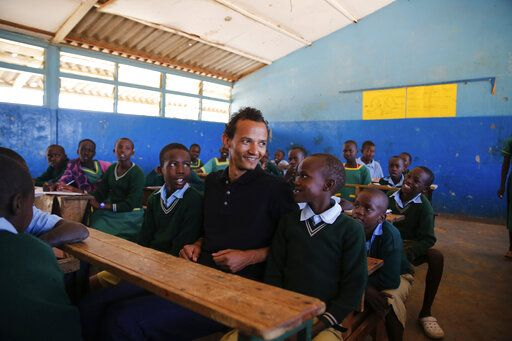 Gerald Erebon sits with students at his old primary school where he said kids used to be tease him about him being the priest's son, in the Isiolo area of the Archers Post settlement in Kenya on Sunday, June 30, 2019. The Vatican is investigating Erebon's claim that his father is the Rev. Mario Lacchin, an Italian missionary priest who impregnated his mother soon after she turned 16.