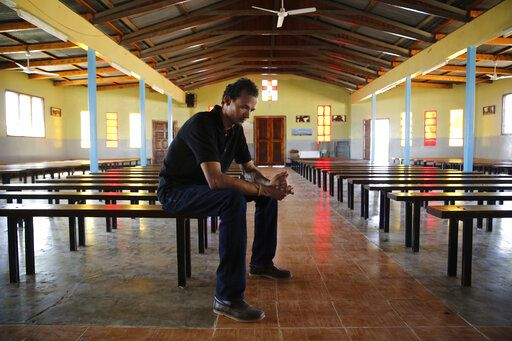 Gerald Erebon sits for a portrait inside Mary Immaculate Catholic Church in the Isiolo area of the Archers Post settlement in Kenya on Sunday, June 30, 2019. Erebon has been an outcast all his life: Tall, light-skinned with wavy hair, Erebon looks nothing like the dark-skinned Kenyan man listed as his father on his birth certificate, or his black mother or siblings. He and his family say that's because his biological father is the Rev. Mario Lacchin, an Italian priest of the Consolata Missionaries order who ministered in Archer's Post, Kenya in the 1980s.
