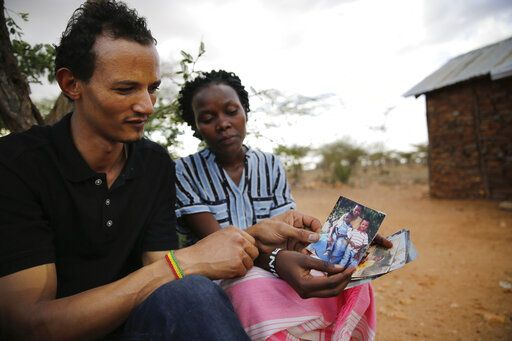 Gerald Erebon and his sister, Lina Ben, hold photos of them and their mother, Sabina Losirkale, who passed away in 2012 after a long illness and depression, in the Isiolo area of the Archers Post settlement in Kenya on Sunday, June 30, 2019. When Lina was 14, she asked her mother why Gerald didn't look like her other children, and why his friends often referred to him as 'œmtoto was padre'� _ 'œchild of the priest.'� Her mother initially pushed her away, but eventually told her that 'œDad to Gerald is a priest called Father Mario and he is not here.'�