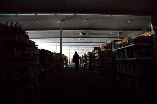 Shift supervisor James Quinn walks through a darkened CVS Pharmacy as downtown Sonoma, Calif., remains without power on Wednesday, Oct. 9, 2019. Pacific Gas and Electric has cut power to more than half a million customers in Northern California hoping to prevent wildfires during dry, windy weather throughout the region.