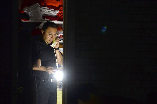Daniel Almanza of Bayside Cafe, which was among businesses to lose power due to PG&E's public safety power shutoff, calls a supplier from the office of the restaurant in Sausalito, Calif., Wednesday, Oct. 9, 2019. Pacific Gas & Electric has cut power to more than half a million customers in Northern California hoping to prevent wildfires during dry, windy weather throughout the region. (Alan Dep/Marin Independent Journal via AP)