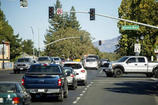 Vehicles backs up on Highway 12 as traffic signals remain dark during a power outage on Wednesday, Oct. 9, 2019, in Boyes Hot Springs, Calif. Pacific Gas and Electric has cut power to more than half a million customers in Northern California hoping to prevent wildfires during dry, windy weather throughout the region.