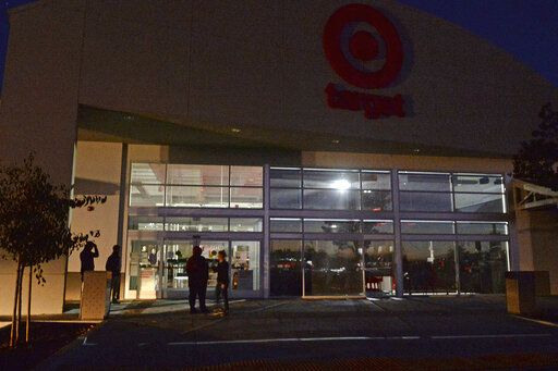 Emergency lights shine inside an otherwise dark Target store at the Gateway Shopping Center in Marin City, Calif, Wednesday, Oct. 9, 2019. Pacific Gas & Electric has cut power to more than half a million customers in Northern California hoping to prevent wildfires during dry, windy weather throughout the region. (Alan Dep/Marin Independent Journal via AP)