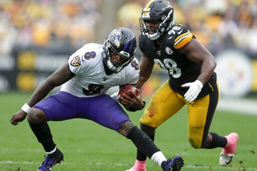 Baltimore Ravens quarterback Lamar Jackson (8) scrambles away from Pittsburgh Steelers inside linebacker Vince Williams (98) in the second half of an NFL football game, Sunday, Oct. 6, 2019, in Pittsburgh.