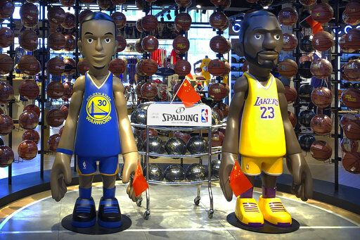 Statues of NBA players Stephen Curry of the Golden State Warriors, left, and Lebron James of the Los Angeles Lakers hold Chinese flags in the entrance of an NBA merchandise store in Beijing, Tuesday, Oct. 8, 2019. Chinese state broadcaster CCTV announced Tuesday it will no longer air two NBA preseason games set to be played in the country.