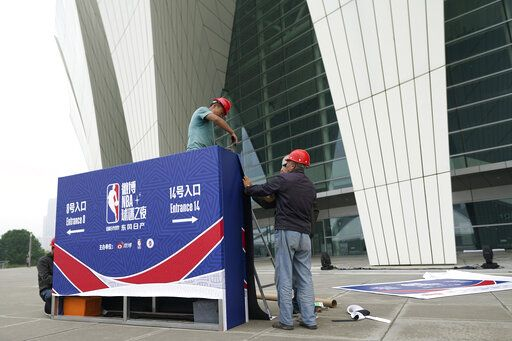 Workers dismantle signage for an NBA fan event scheduled to be held on Wednesday night at the Shanghai Oriental Sports Center in Shanghai, China, Tuesday, Oct. 8, 2019. Chinese state broadcaster CCTV announced Tuesday it will no longer air two NBA preseason games set to be played in the country.