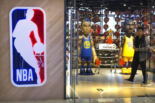 A man walks past statues of NBA players Stephen Curry of the Golden State Warriors, left, and Lebron James of the Los Angeles Lakers holding Chinese flags in the entrance of an NBA merchandise store in Beijing, Tuesday, Oct. 8, 2019. Chinese state broadcaster CCTV announced Tuesday it will no longer air two NBA preseason games set to be played in the country.