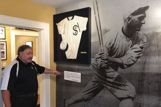 In this Sept. 29, 2019, photo, Michael Wallach, managing director of the Shoeless Joe Jackson Museum, looks at replica of a Joe Jackson jersey in Greenville, S.C.