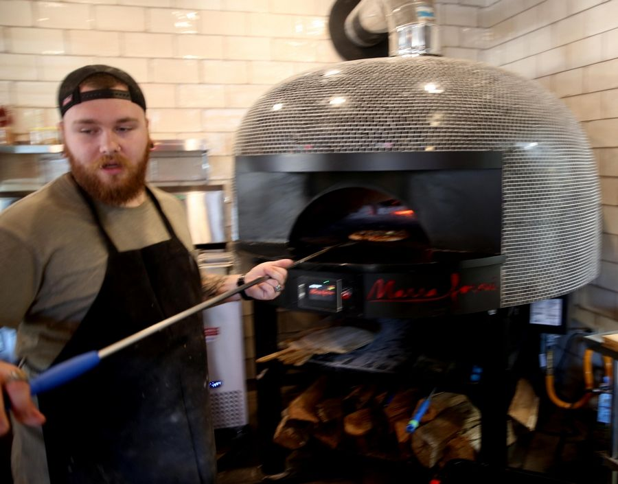 Pizza chef Blaike Kirby prepares a pizza in the wood fire brick oven at West Dundee's Woodfire Brick Oven Pizza.
