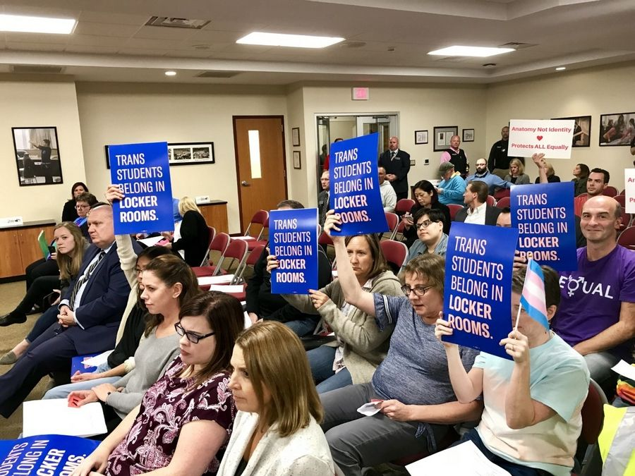 Sections of the crowd at Thursday's Palatine Schaumburg High School District 211 meeting show their support of a proposed policy that would allow transgender students to have unrestricted locker room access.