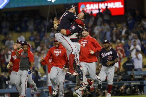 Washington Nationals pitcher Sean Doolittle, left, and catcher Yan Gomes leap in celebration after the team's 7-3 win in Game 5 of a baseball National League Division Series against the Los Angeles Dodgers on Wednesday, Oct. 9, 2019, in Los Angeles.