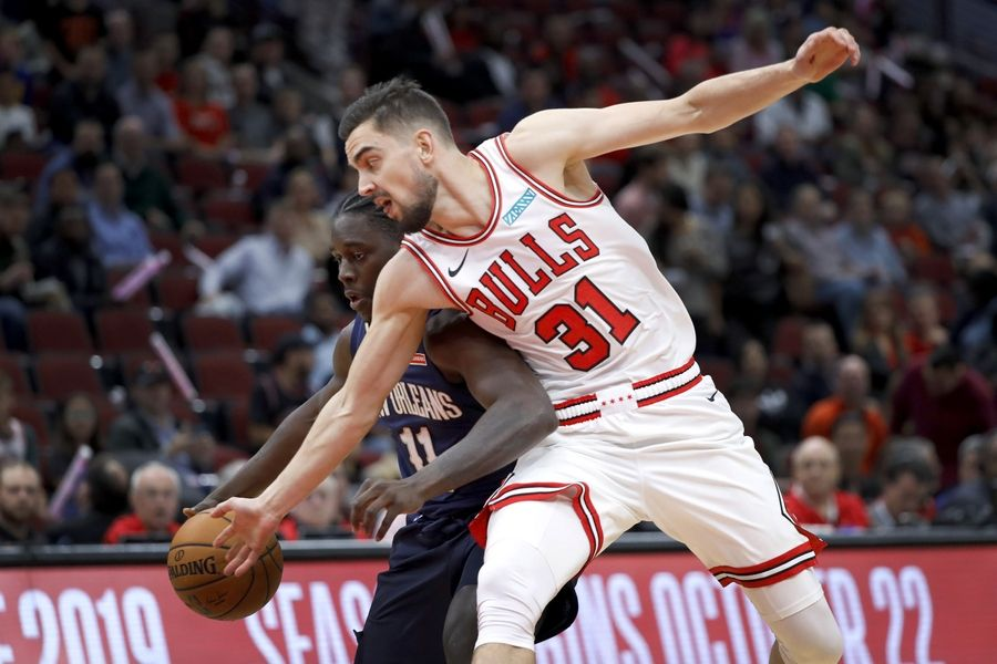 New Orleans Pelicans' Jrue Holiday (11) drives to the basket as Chicago Bulls' Tomas Satoransky defends during the first half of an NBA preseason basketball game Wednesday, Oct. 9, 2019, in Chicago.
