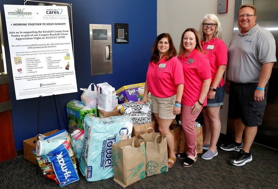 Foundation Wealth Strategies employees, from left, Rosanne Grenfell, Andrea Ortiz, Judy Nelson and Timothy Rueter pose with some of the donations going to Kendall County Community Food Pantry.