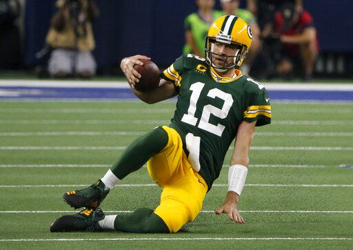 Green Bay Packers quarterback Aaron Rodgers slides to the ground after running the ball during the second half of the team's NFL football game against the Dallas Cowboys in Arlington, Texas, Sunday, Oct. 6, 2019.