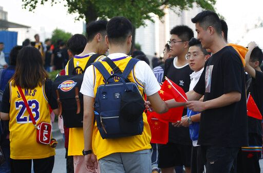Fans hand out Chinese national flags to others arriving for the NBA preseason game to be held at the Mercedes Benz Arena in Shanghai, China, Thursday, Oct. 10, 2019. All media events such as news conferences have been canceled inside the arena hosting Thursday's NBA preseason game in China between the Los Angeles Lakers and Brooklyn Nets, though the matchup itself remains on as scheduled. (AP Photo) /// DQo=