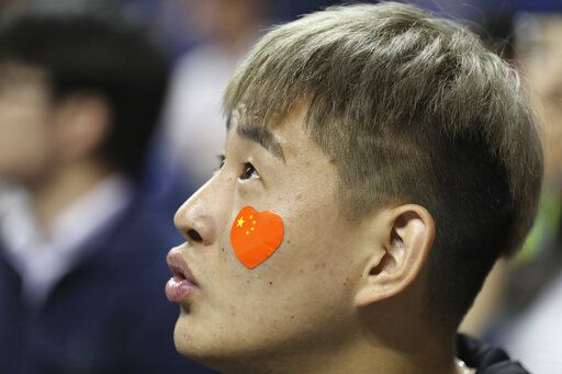 A fan with a heart-shaped Chinese national flag sticker on his face watches a preseason NBA basketball game between the Brooklyn Nets and Los Angeles Lakers at the Mercedes Benz Arena in Shanghai, China, Thursday, Oct. 10, 2019.