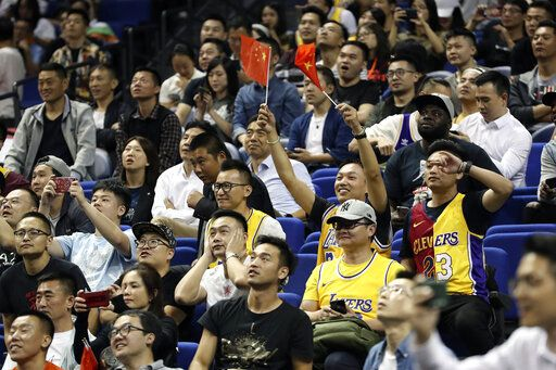 A Chinese fan holds Chinese national flags as he cheers with other fans during a preseason NBA basketball game between the Brooklyn Nets and Los Angeles Lakers at the Mercedes Benz Arena in Shanghai, China, Thursday, Oct. 10, 2019.