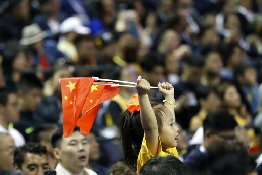 A child holds up two Chinese national flags as she watches a preseason NBA basketball game between the Brooklyn Nets and Los Angeles Lakers at the Mercedes Benz Arena in Shanghai, China, Thursday, Oct. 10, 2019.