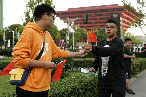 A  man hands out national flags to others arriving for the NBA preseason game to be held at the Mercedes Benz Arena in Shanghai, China, Thursday, Oct. 10, 2019. All media events such as news conferences have been canceled inside the arena hosting Thursday's NBA preseason game in China between the Los Angeles Lakers and Brooklyn Nets, though the matchup itself remains on as scheduled.