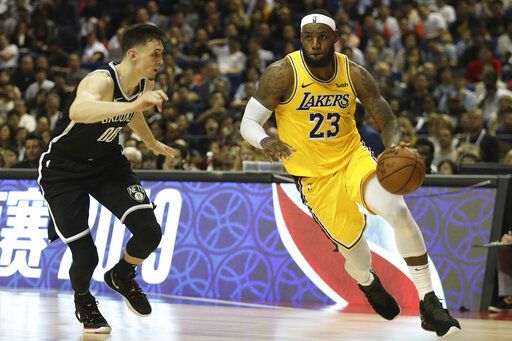 Los Angeles Lakers' Lebron James, right, drives against Brooklyn Nets' Rodions Kurucs, left, during their preseason NBA game in Shanghai, China, Thursday, Oct. 10, 2019.  In response to the NBA defending Daryl Morey's freedom of speech, Chinese officials took it away from the Los Angeles Lakers and Brooklyn Nets, with the usual media sessions canceled in Shanghai, including a scheduled news conference from NBA Commissioner Adam Silver and postgame news conferences with the teams. (AP Photo) /// DQo=