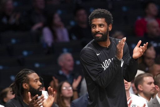 Brooklyn Nets guard Kyrie Irving reacts as he watches the action against the Sesi/Franca Basketball Club from the bench during the first half of a exhibition NBA basketball game, Friday, Oct. 4, 2019, in New York.