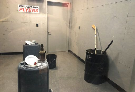 "Hockey sticks sit in a barrel, right, in the ""Rage Room"" before the Philadelphia Flyers' NHL hockey game against the New Jersey Devils on Wednesday, Oct. 9, 2019, in Philadelphia. Grab a helmet and baseball bat and step up to the plate - Flyers fans can take a swing for fun or just to take out frustrations on bottles, dishes or even a fishbowl stamped with the visitor's logo."