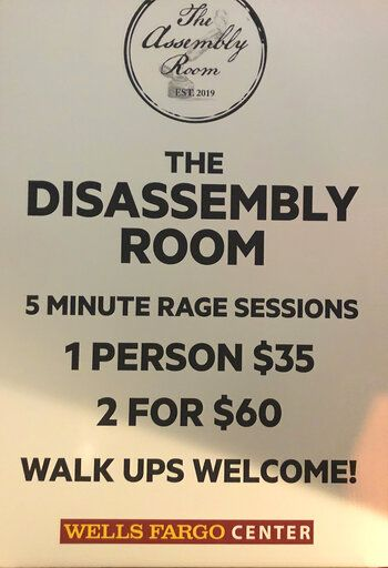 "A sign shows the cost and time allowed in the ""Rage Room"" at Wells Fargo Center, before an NHL hockey game between the Philadelphia Flyers and the New Jersey Devils on Wednesday, Oct. 9, 2019. The room is nestled in the upper level for fans in the new $25 standing-room-only section."