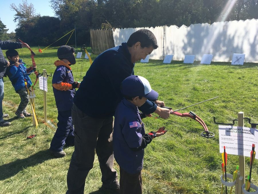 Giliberto Kuzuhara, left, and his son Victor, of Des Plaines, practice archery during the Future Frontier scouting camporee Saturday in Busse Woods Forest Preserve.