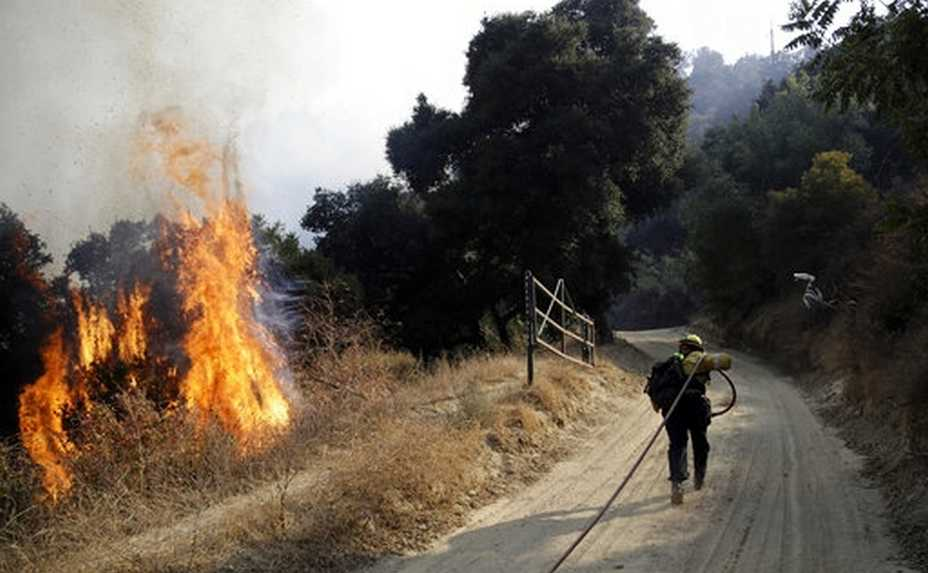 A firefighter runs up a fire road to hose down flames from a wildfire Saturday, Oct. 12, 2019, in Newhall, Calif. Los Angeles Fire Department spokesman Brian Humphrey said the bulk of the fire at the city's edge had moved away from homes and into rugged hillsides and canyons where firefighters were making steady progress slowing its advance. (AP Photo/Marcio Jose Sanchez)