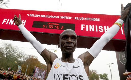 Marathon runner Eliud Kipchoge from Kenya celebrates under the clock after crossing the finish line of the INEOS 1:59 Challenge after 1:59:40 in Vienna, Austria, Saturday, Oct. 12, 2019. He is the first human ever to run a marathon under two hours.