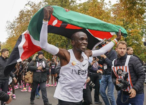 Eliud Kipchoge celebrates with the Kenyan flag after breaking the historic two hour barrier for a marathon in Vienna, Saturday, Oct. 12, 2019. Eliud Kipchoge has become the first athlete to run a marathon in less than two hours, although it will not count as a world record. The Olympic champion and world record holder from Kenya clocked 1 hour, 59 minutes and 40 seconds Saturday at the INEOS 1:59 Challenge, an event set up for the attempt. (Jed Leicester/The INEOS 1:59 Challenge via AP)