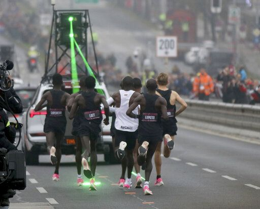 Marathon runner Eliud Kipchoge from Kenya, white vest, and his first pacemaking team run on the Reichsbrucke during the INEOS 1:59 Challenge attempt to run a sub two-hour marathon in Vienna, Austria, Saturday, Oct. 12, 2019.
