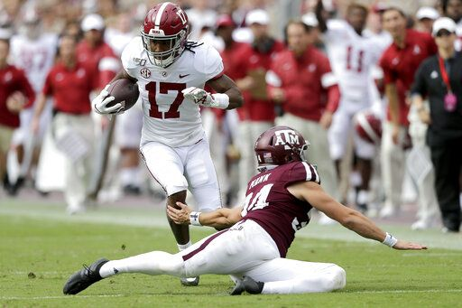Alabama wide receiver Jaylen Waddle (17) jukes Texas A&M punter Braden Mann (34) during a punt return during the first half of an NCAA college football game, Saturday, Oct. 12, 2019, in College Station, Texas.