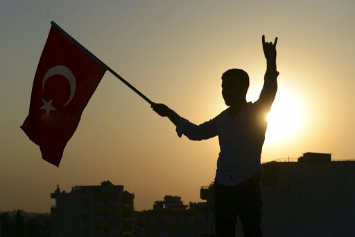 A Turkish youth celebrates with a national flag after news about Syrian town of Tal Abyad, in Turkish border town of Akcakale, in Sanliurfa province, Sunday, Oct. 13, 2019. Turkey's official Anadolu news agency, meanwhile, said Turkey-backed Syrian forces have advanced into the center of a Syrian border town, Tal Abyad, on the fifth day of Turkey's military offensive. (Ismail Coskun/IHA via AP)