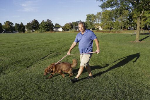 Mark Stenske walks his dog, Leo, as he discusses the impeachment inquiry into President Donald Trump while walking in a park, Wednesday, Oct. 9, 2019, in Fishers, Ind.