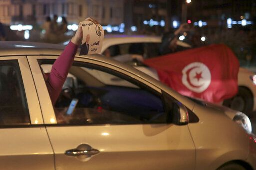 Peopel celebrate with a poster of Kais Saied and Tunisian flags in Tunis, Sunday, Oct. 13, 2019. Tunisian polling agencies are forecasting that conservative law professor Kais Saied has overwhelmingly won the North African country's presidential election.
