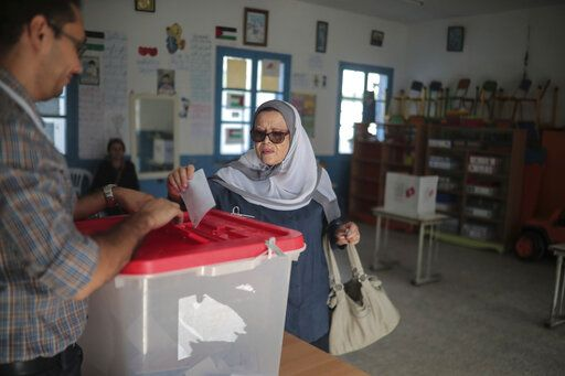 A woman casts her ballot during the second round of the presidential election, in Tunis, Tunisia, Sunday, Oct. 13, 2019. Tunisians are voting for president, choosing between a law professor and populist tycoon.
