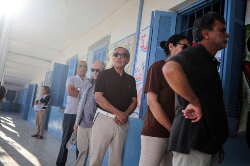 People queue outside a polling station during the second round of the presidential election, in Tunis, Tunisia, Sunday, Oct. 13, 2019. Tunisians are voting for president, choosing between a law professor and populist tycoon.