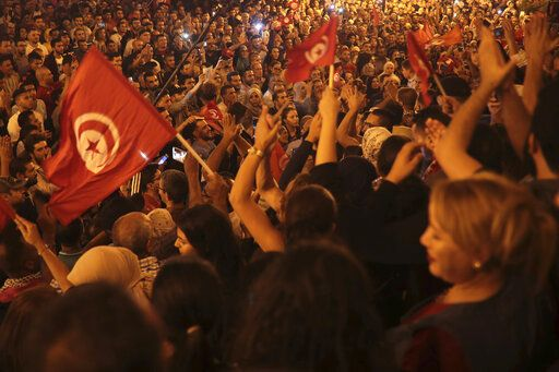 A crowd gathers on Tunis' main avenue, Sunday, Oct. 13, 2019. Tunisian polling agencies are forecasting that conservative law professor Kais Saied has overwhelmingly won the North African country's presidential election.