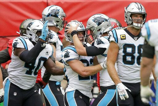 Carolina Panthers running back Christian McCaffrey (22) is congratulated by quarterback Kyle Allen after scoring a touchdown against the Tampa Bay Buccaneers during the first quarter of an NFL football game, Sunday, Oct. 13, 2019, at Tottenham Hotspur Stadium in London.