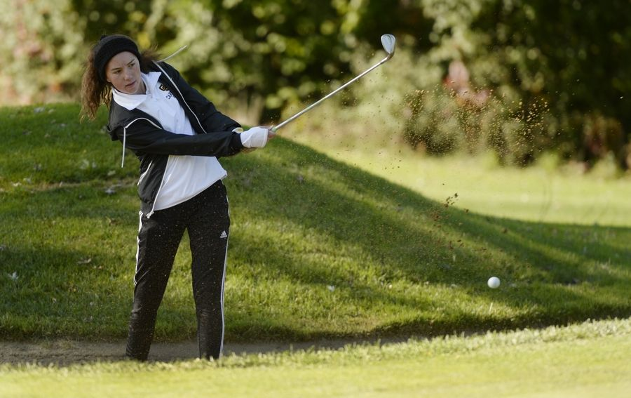 The first hole found Carmel's Maria Stephens chipping out of the sand trap in the Class 2A Prospect girls golf sectional in Mount Prospect on Monday.