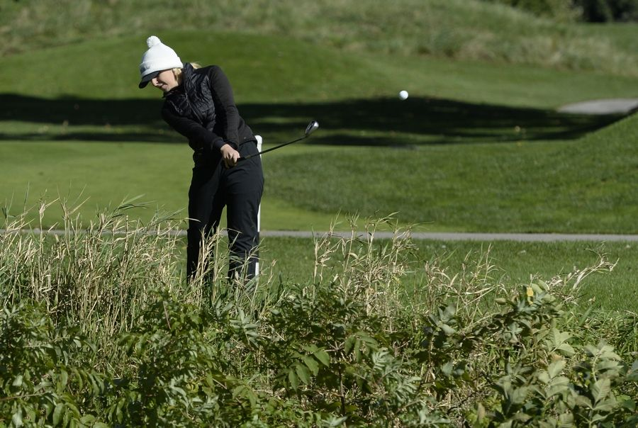 Huntley's Katie Matustik watches the flight of her chip shot on hole No. 17 in the Class 2A Prospect girls golf sectional in Mount Prospect on Monday.