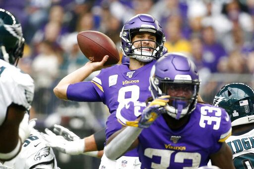 Minnesota Vikings quarterback Kirk Cousins, center, throws a pass during the first half of an NFL football game against the Philadelphia Eagles, Sunday, Oct. 13, 2019, in Minneapolis.