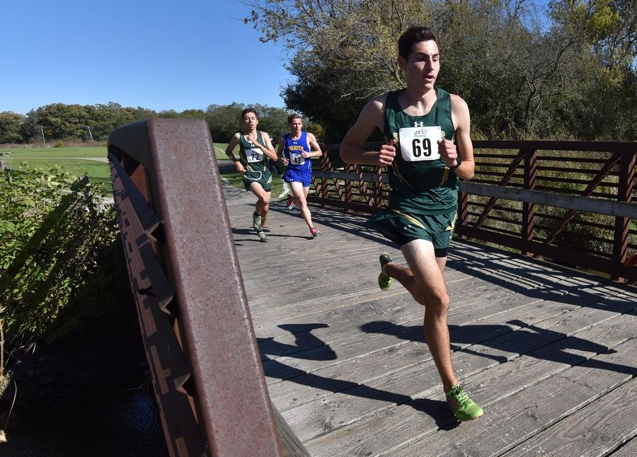 Eventual winner Corey Pacernick, of Stevenson High School, left, crosses a bridge at the North Suburban Conference cross country meet at Lake Forest High School west campus Saturday.